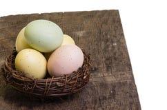 Os pássaros aninham-se completamente de ovos coloridos na tabela Imagens de Stock Royalty Free