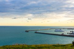 Os pássaros circundam enquanto um navio entra no porto no por do sol imagem de stock royalty free
