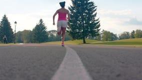 Os pés africanos da mulher em sapatas do esporte começam correr na estrada asfaltada filme