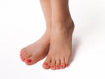 Os pés bonitos com termas perfeitos pregam o pedicure no fundo branco Fotografia de Stock