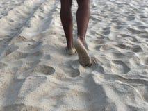 Os pés bronzeados dos homens na areia fina branca da praia original de Karon de Phuket no fundo do mar e do por do sol dourado, foto de stock royalty free