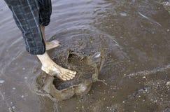 Os pés chapinham a poça de lama Imagem de Stock