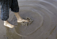 Os pés chapinham a poça de lama Fotografia de Stock