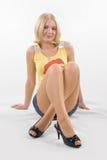 Os pés cruzaram-se no miniskirt Imagens de Stock