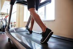 Os pés da aptidão nova equipam o corredor na escada rolante no gym fotos de stock royalty free