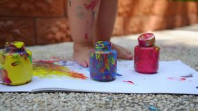 Os pés da criança tiram uma pintura do dedo - azul, vermelha e amarela em uma folha de papel branca Desenvolvimento infantil cria vídeos de arquivo