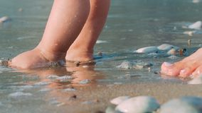 Os pés da mãe e do bebê que andam na areia encalham Pés recém-nascidos da criança na praia filme