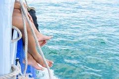 Os pés da menina penduram fora do barco de passageiro da borda no oceano fotografia de stock royalty free