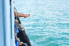 Os pés da menina penduram fora do barco de passageiro da borda no oceano foto de stock
