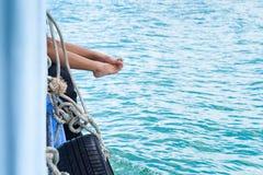 Os pés da menina penduram fora do barco de passageiro da borda no oceano imagens de stock royalty free