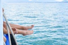 Os pés da menina penduram fora do barco de passageiro da borda no oceano fotos de stock