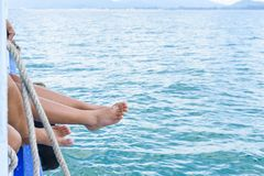 Os pés da menina penduram fora do barco de passageiro da borda no oceano fotos de stock royalty free