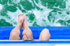 Os pés da menina penduram fora do barco de passageiro da borda no oceano Olhe a parte superior fotos de stock royalty free