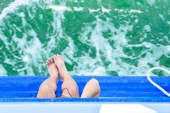 Os pés da menina penduram fora do barco de passageiro da borda no oceano Olhe a parte superior fotografia de stock royalty free