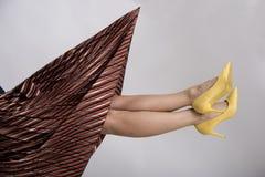 Os pés da mulher acima no ar com as sapatas colocadas saltos altas amarelas fotos de stock royalty free