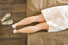 Os pés da mulher em detalhe Encontro na cama no vestido de pingamento curto fotografia de stock royalty free