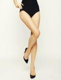 Os pés da mulher em sapatas pretas alto-colocadas saltos Fotos de Stock Royalty Free