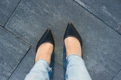 Os pés da mulher em sapatas pretas clássicas no asfalto do cinza do ` s da cidade Vista de acima fotos de stock