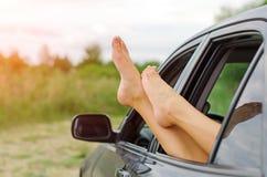 Os pés da mulher fora do carro Fotos de Stock Royalty Free