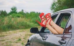 Os pés da mulher fora do carro Imagens de Stock
