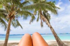 Os pés da mulher no fundo tropical da praia e do mar, vacati do verão Imagem de Stock