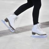 Os pés da mulher nos patins de gelo brancos imagens de stock