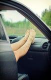 Os pés da mulher que encontram-se no carro Fotografia de Stock