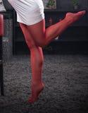 Os pés da mulher vestem calças justas vermelhas Fotos de Stock