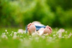 Os pés das crianças na grama fora Imagens de Stock