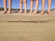 Os pés das crianças na praia Imagem de Stock