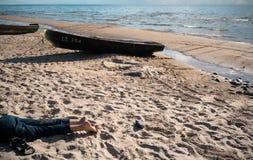 Os pés das crianças na praia contra o contexto de um barco velho Foto de Stock Royalty Free