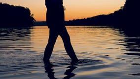 Os pés das mulheres elegantemente e vão graciosamente joelho profundamente no lago no escarlate do por do sol video estoque
