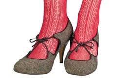 Os pés das mulheres em calças justas delicadas vermelhas com sapatas retros Fotos de Stock