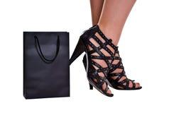 Os pés das mulheres em sapatas wreathy estão atrás do saco Imagem de Stock