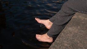 Os pés das mulheres jogam a água Pulverizador, respingo, humor do verão foto de stock