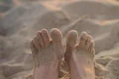 Os pés das mulheres na praia da areia Fotos de Stock