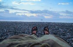 Os pés das mulheres nas calças e nas sandálias nos pés desencapados na zona do por do sol acima do mar encontram-se na praia foto de stock