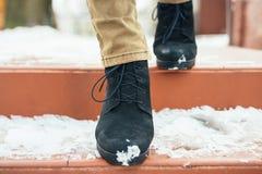 Os pés das mulheres no inverno elegante carreg abaixo da escada coberto de neve Foto de Stock Royalty Free