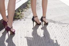 Os pés das mulheres que mostram lhe sapatas do salto alto Fotos de Stock Royalty Free