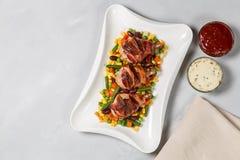 Os pés de frango frito envolveram no bacon com vegetais A vista da parte superior Cópia-espaço fotografia de stock
