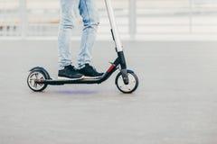 Os pés de homem desconhecido em passeios pretos das sapatilhas e das calças de brim no 'trotinette' bonde sobre o asfalto urbano, imagem de stock