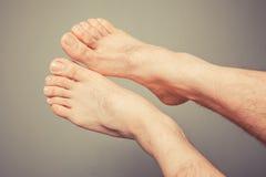 Os pés de homem novo Imagens de Stock