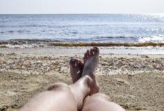 Os pés de um homem em um fundo da praia Um homem encontra-se em um amatra Imagem de Stock Royalty Free