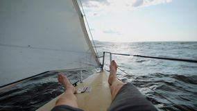 Os pés de um homem que estão no nariz de um iate, pessoa vão pelo barco ao longo das ondas do mar à distância, a vela são filme