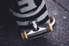 Os pés de um indivíduo nas sapatilhas com um skate na rua Close-up da roda e da suspensão do patim Imagens de Stock Royalty Free