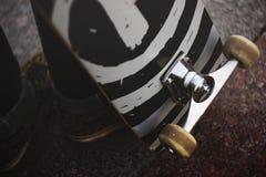 Os pés de um indivíduo nas sapatilhas com um skate na rua Close-up da roda e da suspensão do patim Fotos de Stock