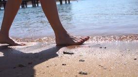 Os pés de uma moça que ande na areia molhada com mar acenam video estoque