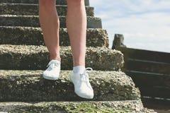 Os pés de uma mulher que anda abaixo das escadas Fotografia de Stock