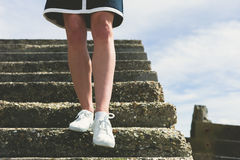 Os pés de uma mulher que anda abaixo das escadas Fotografia de Stock Royalty Free