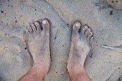 Os pés dos homens na areia Imagens de Stock